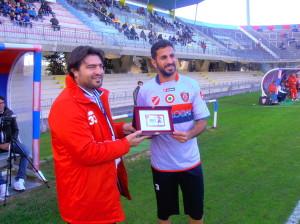 Il difensore Scudieri premiato da Fabio Cristofaro per le 100 presenze in rossoblù