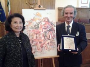 Il maestro Domenico Fratianni accanto a un'opera che raffigura la sua città, Campobasso, con l'assessore de Capoa