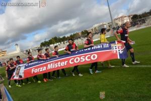 I calciatori della Torres con lo striscione di incoraggiamento per il loro ex allenatore Vincenzo Cosco (foto sito ufficiale Torres)