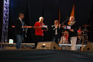 Il sindaco Antonio Battista premia Carmine Brasiliano. Sul palco anche Lello Musella